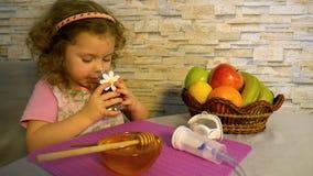En kall liten flicka dricker örtte, hem- behandling stock video