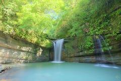 En kall uppfriskande vattenfall in i ett smaragddamm som döljas i en mystisk skog av frodig grönska Royaltyfria Foton