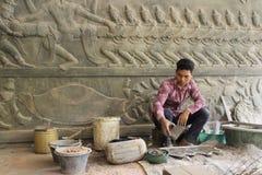 En kambodjansk man tror gjuter en konst som ska dekoreras på tempelväggen Arkivfoton