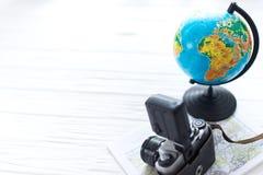 En kamera med ett jordklot på en vit träbakgrund Sats för handelsresande` s Royaltyfri Bild