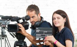 En kameraman och en ung kvinna med kameran Arkivbilder