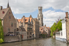 En kanal i Bruges, Belgien, med den berömda klockstapeln i bakgrunden Arkivfoto
