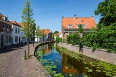 En kanal i den härliga historiska mitten av den gamla byn av Maasland, Nederländerna royaltyfri bild