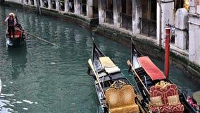 En kanal med två gondoler och en gondoljär som svävar nära dem i Venedig, Italien arkivfoton