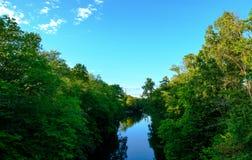 En kanal som omges av träd arkivfoton