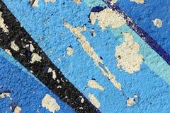 En kanstött vägg som målas med svart- och blåttfärger Arkivfoton