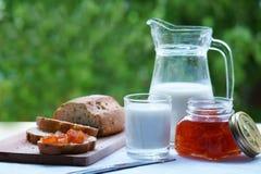 En karaff med mjölkar, och ett exponeringsglas av mjölkar Bröd klipps på ett träbräde Jar av driftstopp Fotografering för Bildbyråer