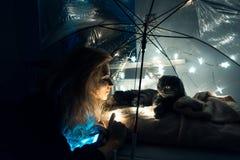 En katt och en kvinna under ett paraply med girlander royaltyfri foto