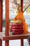 En katt vilar framme av en staty av Buddha i borggården av en tempel (Thailand) Royaltyfria Foton