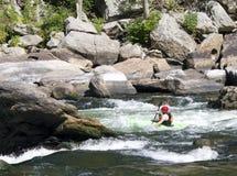 En kayaker skjuter forsarna royaltyfri foto