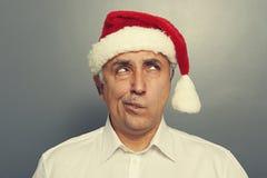 En kerstmanmens die omhoog denken kijken Stock Afbeeldingen