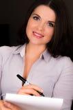 Härligt ungt kvinnligt framlägga med en skriva och skyler över brister Arkivbilder