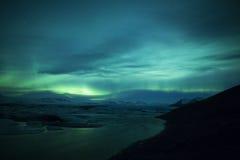 Nordligt tänder ovanför en lagun i Island Arkivfoton