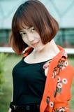 En kinesisk flicka i trädgården Arkivfoto