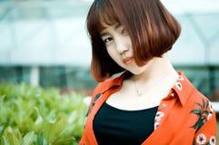 En kinesisk flicka i trädgården Arkivfoton