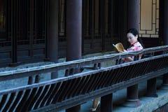 En kinesisk kvinna bär den traditionella klänningen i vattnet parkerar av Shanghai Royaltyfri Bild