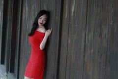 En kinesisk kvinna i den röda klänningen som ligger på en woodern forntida dörr Royaltyfri Foto