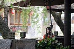 En kinesisk kvinna i röd klänning i Feng Jing den forntida staden Royaltyfri Bild