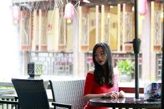 En kinesisk kvinna i röd klänning i Feng Jing den forntida staden Arkivbild