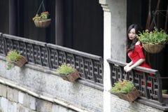 En kinesisk kvinna i röd klänning i Feng Jing den forntida staden Royaltyfri Foto