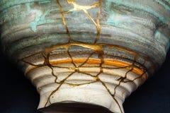 En kintsugi reparerad vas med guld royaltyfri fotografi