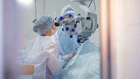 En kirurg och, som assistenten fängslas under en ögonbehandling stock video