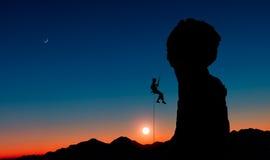 En klättrare som abseiling ner från ett stenigt maximum på solnedgången Royaltyfri Fotografi