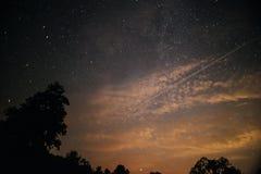 En klar natthimmel med en kulle och träd i förgrunden Royaltyfria Bilder