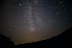 En klar natthimmel med en kulle och träd i förgrunden Royaltyfri Foto