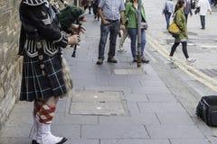 En klarinettspelare, i dess traditionella skotska kilt som direkt utför i kunglig milgata, i stadens centrum Edinburg Royaltyfria Foton