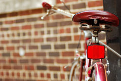 En klassisk cykel låsas upp mot en tegelsten Wal arkivbilder