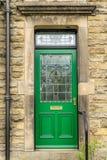 En klassisk traditionell grön dörr med målat glass arkivbild