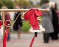En klocka med det röda bandet för bruden och brudgummen Arkivfoton