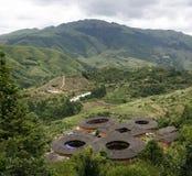 En klunga av Hakka Tulou returnerar förbise dalen och bergskedjan i Yongding Kina Arkivfoto