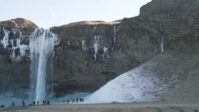 En klunga av turister nära vattenfallet stock video