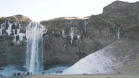 En klunga av turister nära vintervattenfallet stock video