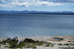 En klyfta ångar bredvid en klar blå kall sjö. Royaltyfri Bild