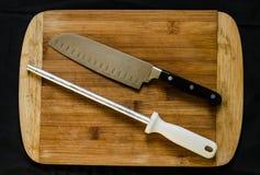 En knivvässare eller honing av stål och av en kockkniv på en skärbräda arkivfoto