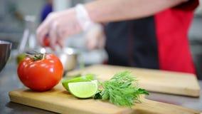 En kock i köket som klipper tomaten Tomat och limefrukt på förgrunden lager videofilmer