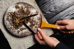 En kock klipper en chokladkaka med en kniv royaltyfria foton