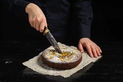 En kock klipper en chokladkaka med en kniv royaltyfri fotografi