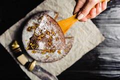 En kock klipper en chokladkaka med en kniv arkivfoto