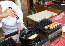 En kock lagar mat en omelett för frukost Arkivfoto