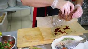 En kock som arbetar i köket Breda smör på stekflott från stekt biff lager videofilmer