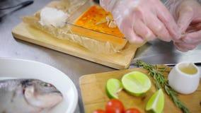 En kock som arbetar i köket Dekorera maträtten med rosmarin arkivfilmer
