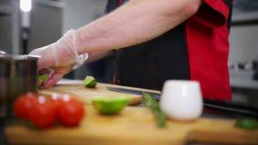 En kock som arbetar i köket Förbereda limefrukten för portion stock video