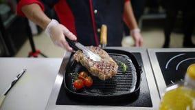 En kock som arbetar i köket Framställning av en stekt biff i pannan stock video