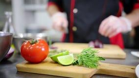 En kock som arbetar i köket Klippa löken En tomat och en limefrukt på förgrunden lager videofilmer