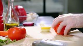 En kock som arbetar i köket Klippa tomaten arkivfilmer