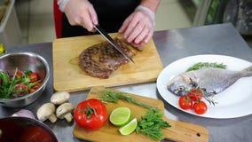 En kock som arbetar i köket En man som klipper en biff arkivfilmer